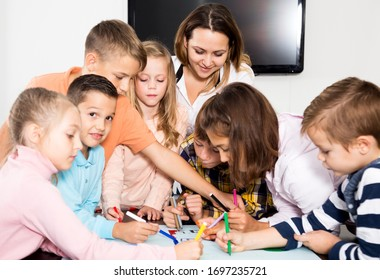 Glad team of elementary age children and female teacher drawing on one sheet