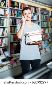 Glad teenage boy chatting on mobile phone and searching book in shop