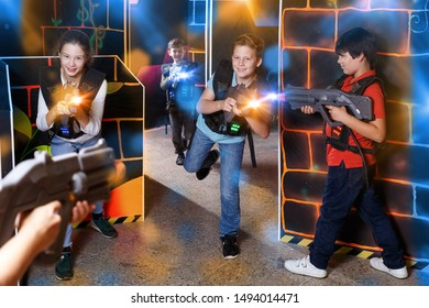 Glad teens aiming laser guns at other players during lasertag game in dark room