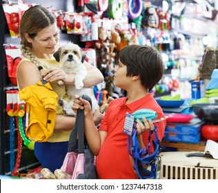 glad tweenager boy and his smiling adult mother looking for supplies for little dog in petshop