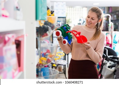 Glad woman in the children's store assortment of plastic toys