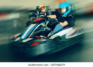 Glad woman driving sport car for karting  in a circuit lap in sport club