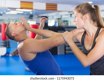 Glad woman is fighting with trainer on the self-defense course for woman in sport club