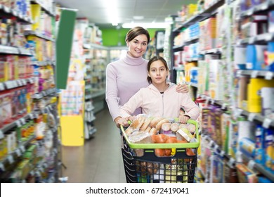 Glad woman with girl shopping with shopping cart in supermarket