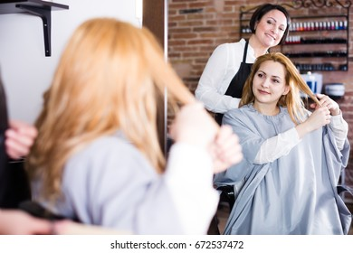 Glad woman in hairdressing salon decides with master how to cut her hair