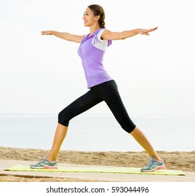 Glad woman practising yoga poses standing on beach by sea at daylight