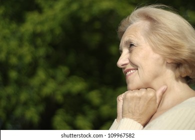Glad woman with short hair on the nature