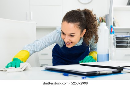 Glad woman in uniform with supplies cleaning in office
