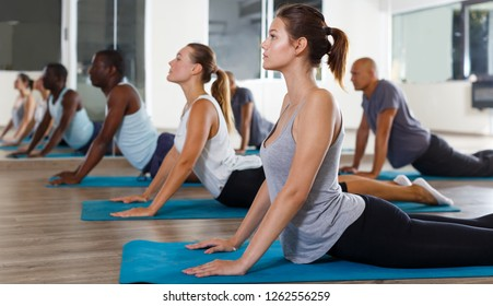 Glad women and men exercising during yoga class in modern fitness center