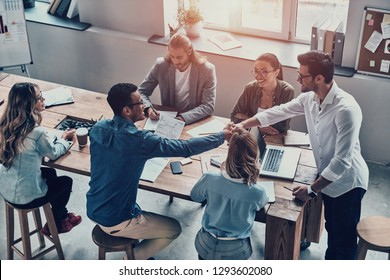 Glad to work with you! Top view of modern young men shaking hands while working in the office