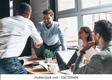 Glad to work with you! Young modern men in smart casual wear shaking hands and smiling while working in the creative office