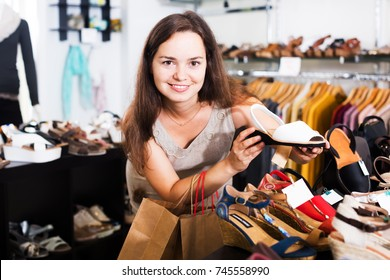Glad young brunette buying summer shoes in footwear shop