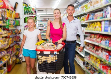 Glad young family of three smiling and standing with purchases in shopping mall