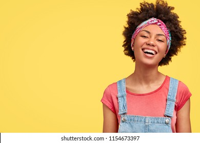 Glad young female with dark skin, white even teeth, laughs positively as sees something funny in front, wears casual t shirt and dungarees, isolated over yellow background with blank space aside