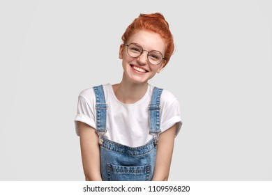 Glad young female with foxy hair, dressed in casual overalls and glasses, poses for magazine article about youth, has broad smile, demonstrates white perfect teeth, stands against concrete wall