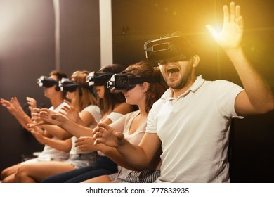 Glad young guy with friends wearing VR headset, interactive touching over air