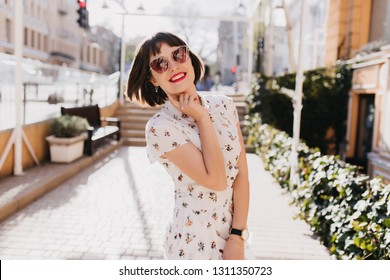 Glad young lady in white dress smiling during outdoor summer photoshoot. Short-haired brunette girl in sunglasses ejoying spring.