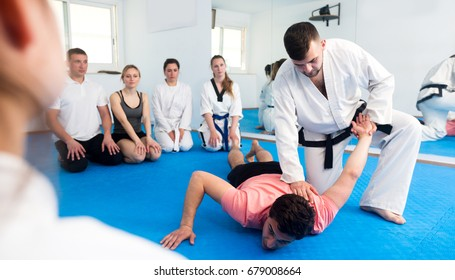 Glad young male coach explaining painful hold to adults in taekwondo class