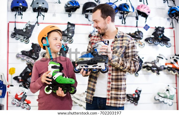 Glad young seller assisting boy in choosing roller-skates in sports store