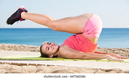 Glad young sporty woman exercising at sea beach