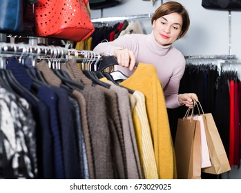 Glad young woman choosing turtleneck sweater in womens cloths shop