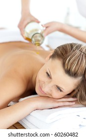 Glad young woman enjoying a back massage with oil in a spa center