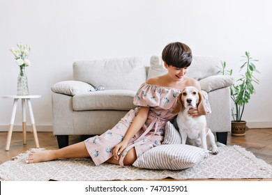 Glad young woman with shiny brown hair posing on the floor with her cute beagle puppy. Indoor portrait of excited girl in dress with floral print sitting on the carpet with dog.