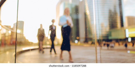 Gladden businesswoman going with blue document case and employees background,  . Concept of blonde female person in white shirt and successful career. Young blonde lady smiling and looking at camera.