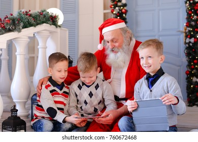 Gladden kids  receiving modern gadget from Santa Claus. Happy children satisfying with winter holidays. Concept of gifting devices for good boys by Father Christmas.