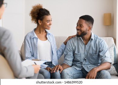 Gladful Black Couple Sitting At Marital Counselor's Office After Happy Marriage Reconciling. Selective Focus