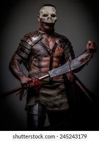 Gladiator in skull mask covered in armor holding sword