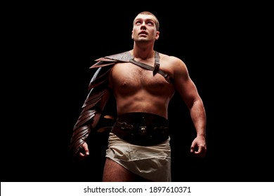 Gladiator with sword and armor on a black background. A warrior in gladiatorial armor looks up at a beam of light