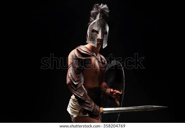 Gladiador con espada y armadura sobre fondo negro