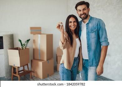 Eine schöne junge Frau, die Schlüssel zu einer neuen Wohnung hält, während sie in der Nähe ihres Freundes steht