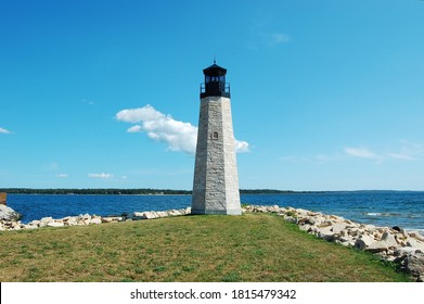 Gladstone Lighthouse in the Upper Peninsula of Michigan on shore of Great Lake Michigan on Green Bay. The waters are visible to horizon.  The Gladstone Michigan Lighthouse stands tall at breakwater. - Shutterstock ID 1815479342