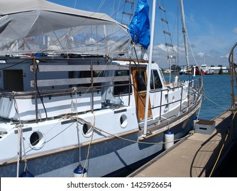 Gladstone Marina. Sailboat tied up to a marina floating walkway in tropical water with blue sky backdrop. Safe haven for sailing and cruising vessels. Gladstone, Queensland, Australia.