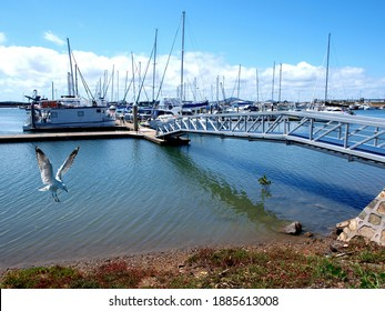 Gladstone Marina. Waterfront walkway with boats in tropical water with blue sky backdrop. Safe haven for sailing and cruising vessels. Gladstone, Queensland, Australia.