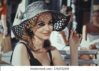 glamor caucasian brunette woman wearing 50s style makeup wearing a black dress and a sun hat having a drink on a terrace and smoking a cigarette outside in the center of Brussels