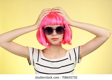 glamor, cute woman with pink hair holds on her head against a yellow background will wither