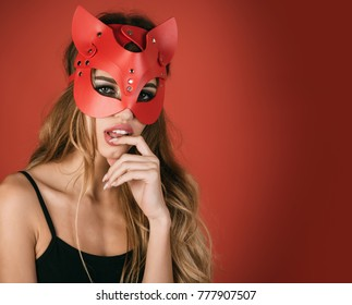 Glamor fashion sexy woman in cat mask. Isolated on red background. Christmas masquerade party, carnival, New Year, halloween concept - sexy portrait of woman wearing cat mask.