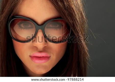 545be27bfd11 Glamor portrait of a beautiful long hair brunette woman wearing sunglasses  studio shot