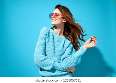 Glamor woman in blue sweater and pink glasses on blue background