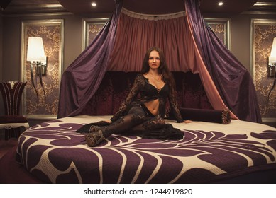 Glamor woman in transparent clothes on bed
