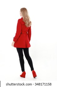 glamorous, beautiful blonde young woman with blonde hair, wearing  long, red winter trench coat.  full length standing portrait,  back view, walking away from camera. isolated on white background.