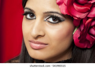 Glamorous beauty fashion image of dark haired middle eastern woman holding a black flower
