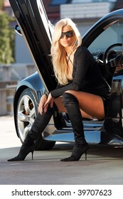 Glamorous blond babe sitting in tuned supercar