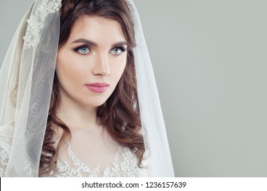 Glamorous bride woman with makeup and veil on background with copy space