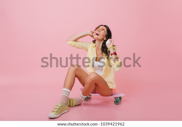 Glamorous brunette girl with tanned skin sitting on longboard with legs crossed. Indoor portrait of romantic hispanic woman in yellow sneakers listening music in headphones.