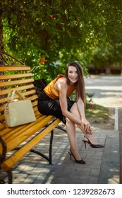 glamorous business girl with a bag sits, straightens the shoes on her foot on a park bench.