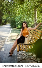 glamorous business girl with a bag sitting on a park bench.